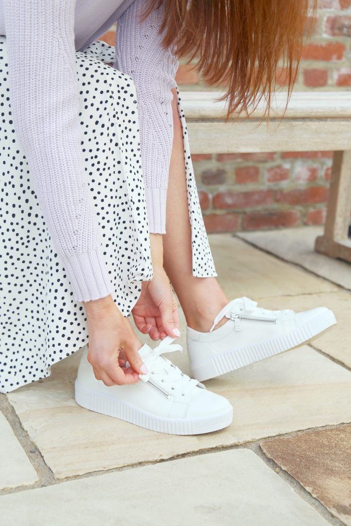 Woman tying laces of white flatform trainers