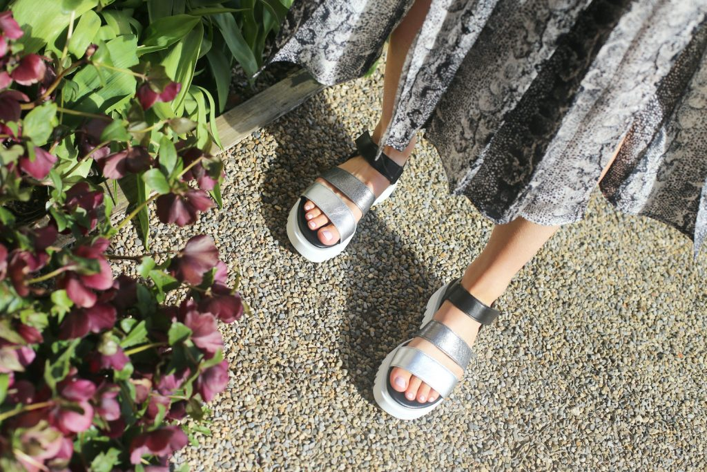 Woman wearing a pair of Gabor Shoes metallic flatform sandals
