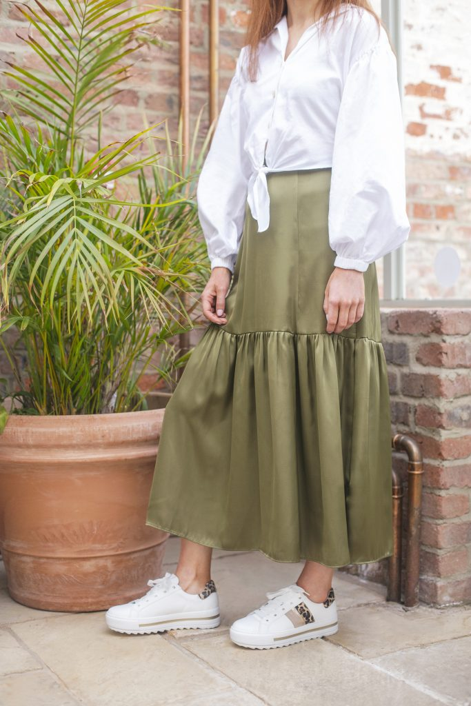 Woman wearing long green maxi skirt with stylish trainers