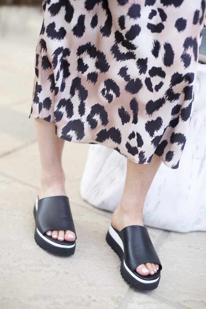 Lady wearing black leather, peep-toe flatform sandals